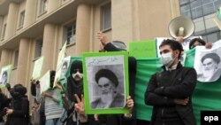 Opposition supporters hold placards with images depicting the late supreme leader of the 1979 Islamic Revolution Grand Ayatollah Ruhollah Khomeini as they stage a demonstration at the Tehran University