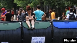 Armenia - A protester sits on a trash container forming part of a barricade on Marshal Bagramian Avenue, Yerevan, 25Jun2015.