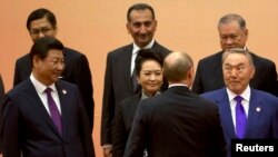 В первом ряду - президент Китая Си Цзиньпин, его супруга Пенг Люян, президент России Владимир Путин (со спины) и президент Казахстана Нурсултан Назарбаев. Шанхай, 20 мая 2014 года.