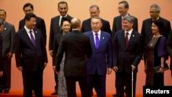 Ресей президенті Владимир Путин (арқасын беріп тұр) АӨСШК-не мүше елдер басшыларымен бірге. Шанхай, Қытай, 20 мамыр 2014 жыл.