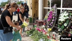 People place flowers outside a gun shop in memory of a salesman who was killed during the June 5 attacks in Aqtobe.