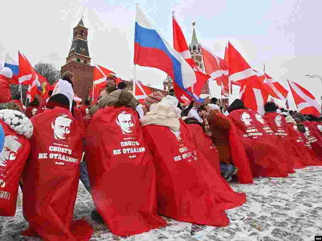 "Russia -- Young people covered in red and decorated with Vladimir Putin's portraits take part in rally of pro-presidential youth movement ""Nashi"" celebrating the victory of United Russia in the elections, in front of Kremlin, 03Dec2007 - 3 грудня, 2007, Москва: «Наші» святкують перемогу «Єдиної Росії» Владіміра Путіна на виборах."