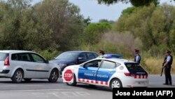 Алканар қаласына кіреберіс жолда Барселонадағы шабуылға күдіктіні ұстау операциясы аясында жолды жауып тұрған полиция қызметкерлері. Испания, 20 тамыз 2017 жыл.