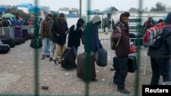 """Migrants with their belongings queue at the start of their evacuation and transfer to reception centers in France, and the dismantlement of the camp called the """"Jungle"""" in Calais on October 24."""