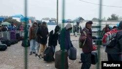 Мигранты из лагеря в Кале в очереди ожидают эвакуации в другие приёмные пункты Франции, 24 октября 2016