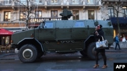 A woman walks past an armored personnel carrier in Brussels on November 23.