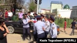 Полицейские уносят одну из протестующих женщин. Алматы, 2 мая 2011 года.
