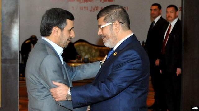 Egyptian President Muhammad Morsi (right) greets his Iranian counterpart, Mahmud Ahmadinejad, in Cairo