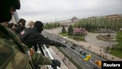 Ռուս ակտիվիստները Դոնեցկում պետական շենքի տանիքից ցած են նետում Ուկրաինայի դրոշը, 28 ապրիլի, 2014թ.
