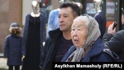 Зейнеткер Раиса Дүйсенбаева (оң жақта) белсенділерді ұстап әкетіп жатқан полицияға наразылық білдіріп тұр. Алматы, 23 қазан 2016 жыл.