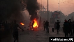 Anti-government protesters set fires and close a street during a demonstration in Baghdad on October 5.