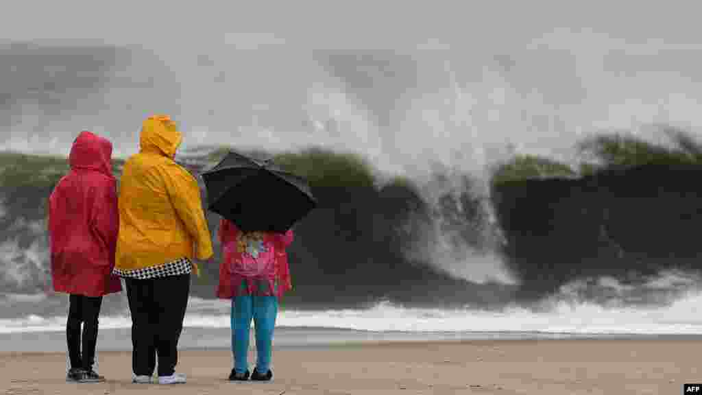 People stand on the beach watching the heavy surf caused by the approaching Hurricane Sandy, Cape May, New Jersey.