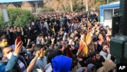 University students attend a protest inside Tehran University while anti-riot Iranian police prevent them to join other protesters, in Tehran, Iran.