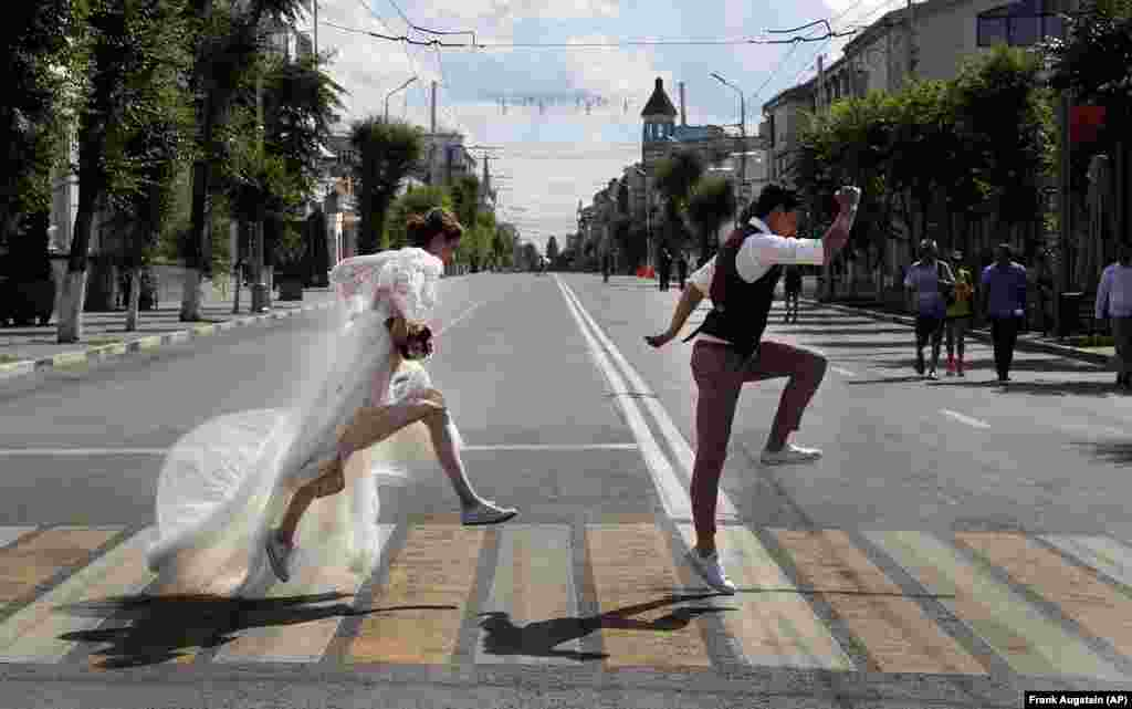 Newlyweds pose on a zebra crossing for wedding photographers during the soccer World Cup in Samara, Russia. (AP/Frank Augstein)