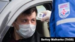 Сотрудник «скорой помощи» измеряет температуру водителю на блокпосту при въезде в Севастополь