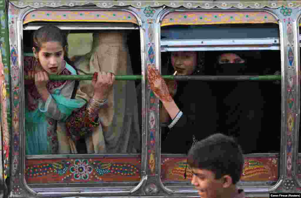 Women riding in a van react to something happening outside in Rawalpindi, Pakistan, on October 5. (Reuters/Caren Firouz)