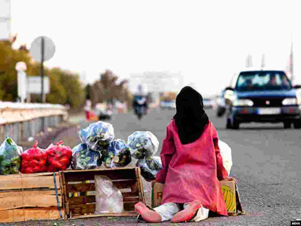 An Iranian girl sells vegetable to passing cars.