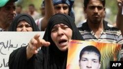 سيدة تحمل صورة ولدها السجين وتطالب باطلاق سراحه