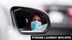 Nje grua mban maskën mbrojtëse derisa gjendet në makinë. Foto është bërë në Kaliforni të SHBA-së.