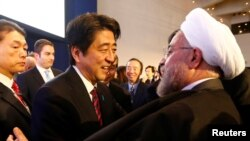 FILE PHOTO: Japan's Prime Minister Shinzo Abe greets Iran's President Hassan Rouhani (R) during the annual meeting of the World Economic Forum (WEF) in Davos January 22, 2014. REUTERS/Denis Balibouse/File Photo