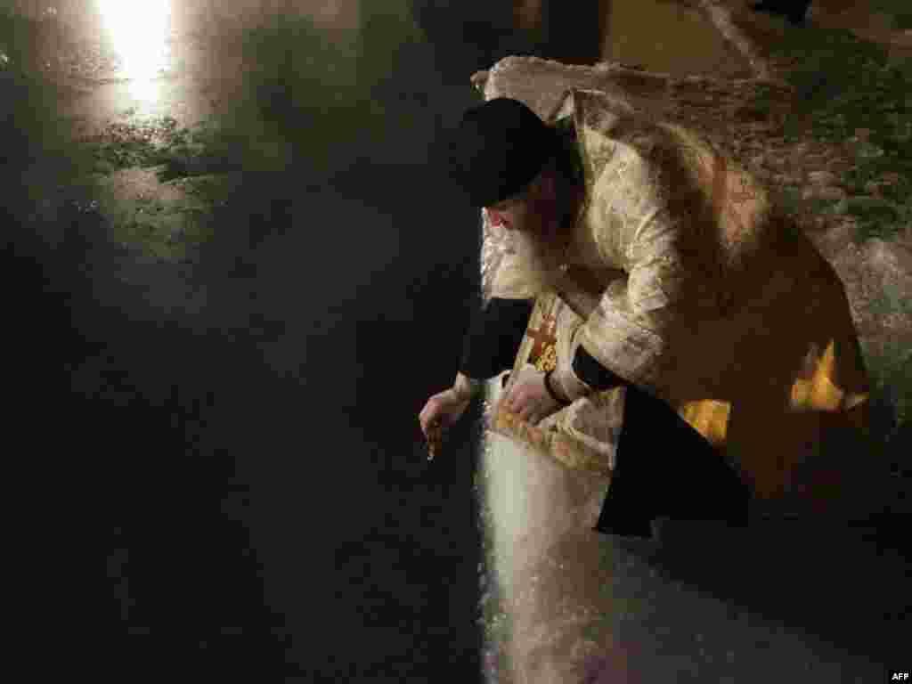 Праваслаўны сьвятар асьвячае проруб у форме крыжа ў адным з элітных маскоўскіх гольф-клюбаў на Вадохрышча.