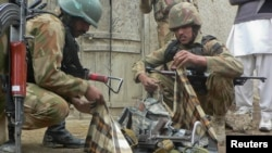 Security officials collect weapons near the site of a police station in Bannu after it was attacked by militants.