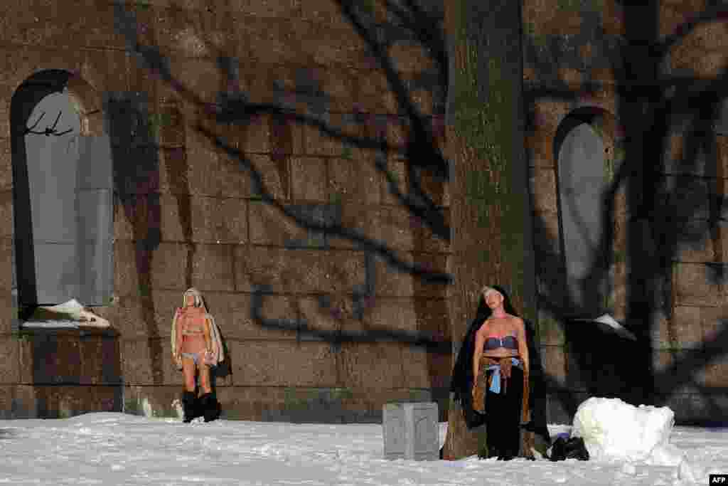 Two women sunbathe at the wall of the Peter and Paul fortress in St. Petersburg. (AFP/Olga Maltseva)