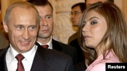 Russian President Vladimir Putin (left) smiles next former Russian gymnast and former Duma deputy Alina Kabayeva, with whom he has been romantically linked. According to the Reuters news agency Kabayeva was implicated in a report on alleged connections between a shadowy Putin-connected businessman and several women in the president's life.