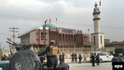 FILE: Afghan security forces keep watch in front of a Shi'a mosque that was targeted in November.