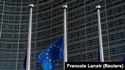 An European Union flag flies outside the EU Commission headquarters in Brussels.