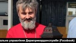 Архиепископ Климент держит Благодатный огонь на админгранице между Крымом и материковой Украиной, Каланчак, 28 апреля 2019 года