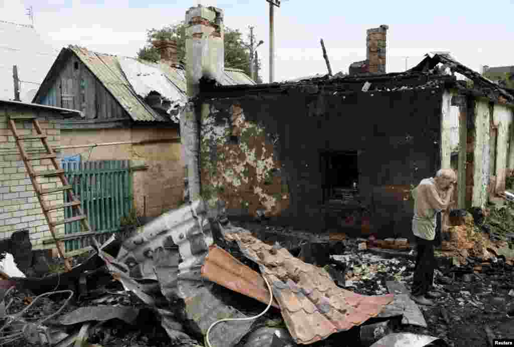 A man cries as he inspects debris while standing outside his damaged house, which, according to locals, was caused by recent shelling, in Donetsk, eastern Ukraine. (Reuters/Alexander Ermochenko)