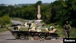 Украина сарбазы істен шыққан танкінің қасынан өтіп барады. Славянск, 5 шілде 2014 жыл.