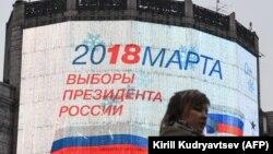 Женщина на фоне огромного монитора с информацией о дате выборов президента России (18 марта 2018 года). Москва, 29 декабря 2017 года.