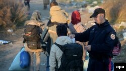 Сербська поліція перевіряє документи мігрантів на кордоні Сербії й Македонії, 19 листопада 2015 року
