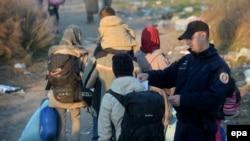 Miratovac, policajac proverava dokumenta izbeglica koje ulaze iz Makedonije