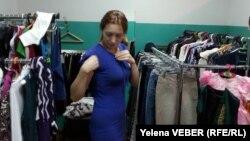 Покупательница примеряет платье в благотворительном магазине. Караганда, 14 декабря 2014 года.