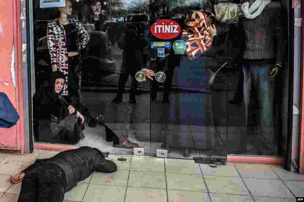 A man lies on the pavement after Turkish antiriot police officers fired tear gas to disperse supporters in front of the headquarters of the Turkish daily newspaper Zaman in Istanbul after Turkish authorities seized the headquarters in a midnight raid. (AFP/Ozan Kose)