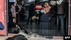 A man lies on the pavement after Turkish antiriot police officers fired tear gas to disperse supporters in front of the headquarters of the Turkish daily newspaper Zaman in Istanbul on March 5.