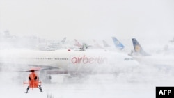 A helicopter lands next to an Air Berlin plane at the airport of Duesseldorf, Germany, one of many airports struggling to cope with the weather.