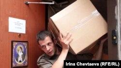 """Волонтер выносит вещи из фонда """"Справедливая помощь"""" в машину для отправки пострадавшим в Крымск, 10 июля 2012 года"""