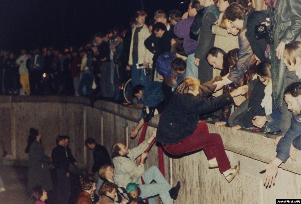 در این تصویر مربوط به ۱۰ نوامبر ۱۹۸۹، شهروندان غرب برلین به ساکنان بخش شرقی آن برای بالا رفتن از دیوار کمک میکنند