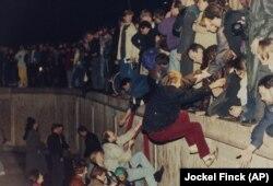 شهروندان برلین غربی در ۱۰ نوامبر ۱۹۸۹ به شهروندان بخش شرقی برلین برای عبور از دیوار کمک میکنند