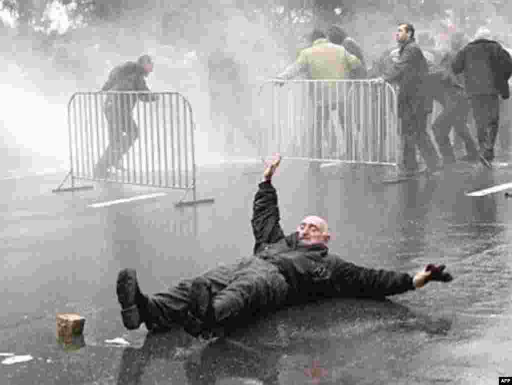 A Georgian opposition supporter falls down as special police forces use water to disperse protesters in front of the parliament building in Tbilisi on November 7, 2007. (AFP photo)