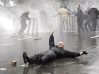 An opposition supporter falls on the street as police disperse protesters in Tbilisi (AFP)