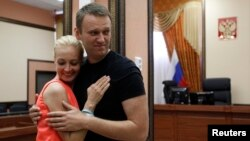 Russian opposition leader Aleksei Navalny embraces his wife, Yulia inside a court building in Kirov in July 2013.