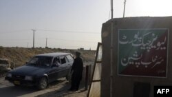A Pakistani security officer searches a car at a checkpoint in Pishin, Baluchistan, in July 2011.