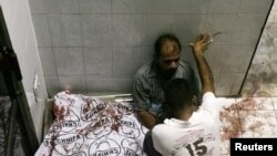 Men grieve next to the body of a relative who was among the victims of the attack on a Karachi market on October 19.