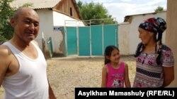 Арыс қаласының тұрғыны Маxамбетжан Бейсебаев әйелі Сәуле және қызымен бірге үйінің алдында тұр. 29 маусым 2019 жыл.