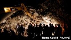 Спасательные работы на месте разрушенных домов в результате землетрясения в Аматриче.
